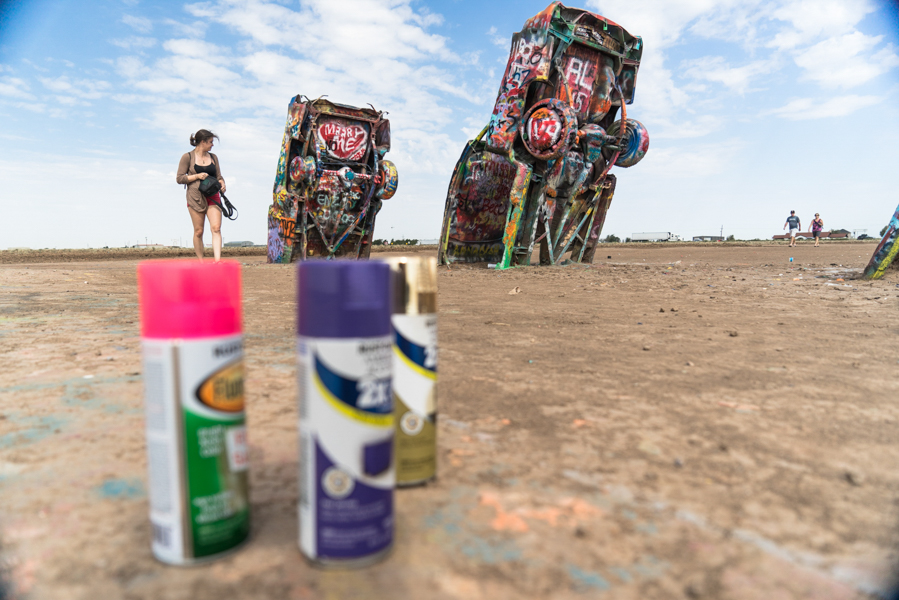 Cadillac Ranch, Amarillo, TX   Cadillac Ranch is one of those places that screams tourist trap. The place is a great stop to break up the monotony of a long drive, however, due to its interactivity.  People are encouraged to take part in the piece and spray paint their own pieces onto the cars.  We did not happen to bring paint with us, but other visitors were more than happy to share their unused supplies with us.  We took some time to climb around and leave our own touch on a few of the cars.