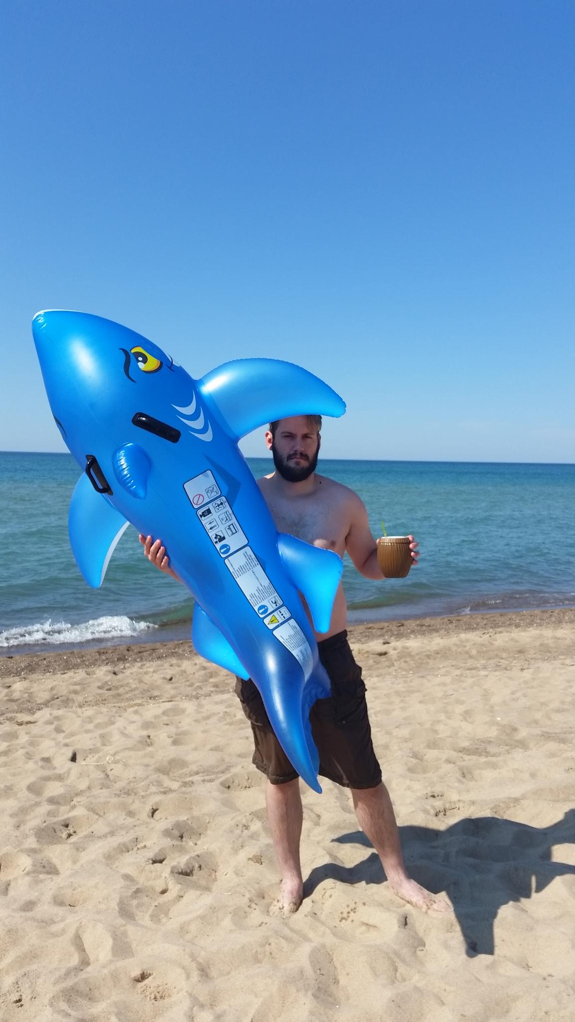 Jason enjoying a beverage & our shark floatie after a swim