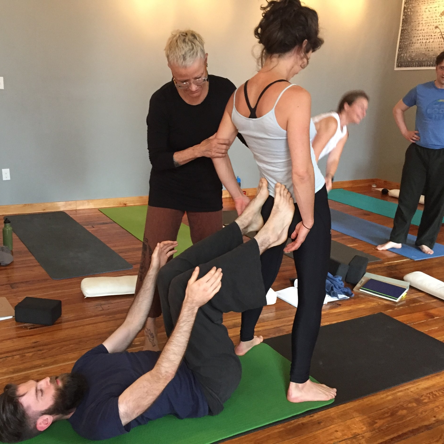 Nina Be showing yoga teachers how to do hands on assists during Yoga Teacher Training