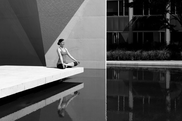 Yogi sitting in meditation over still pond surrounded by modern architecture