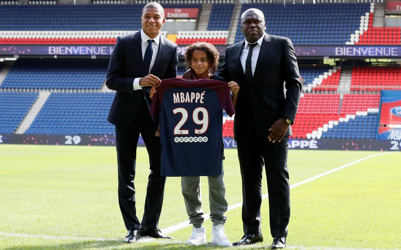 Kylian with his younger brother Ethan and his Father Wilfried. Photo by Reuters/Gonzalo Fuetez