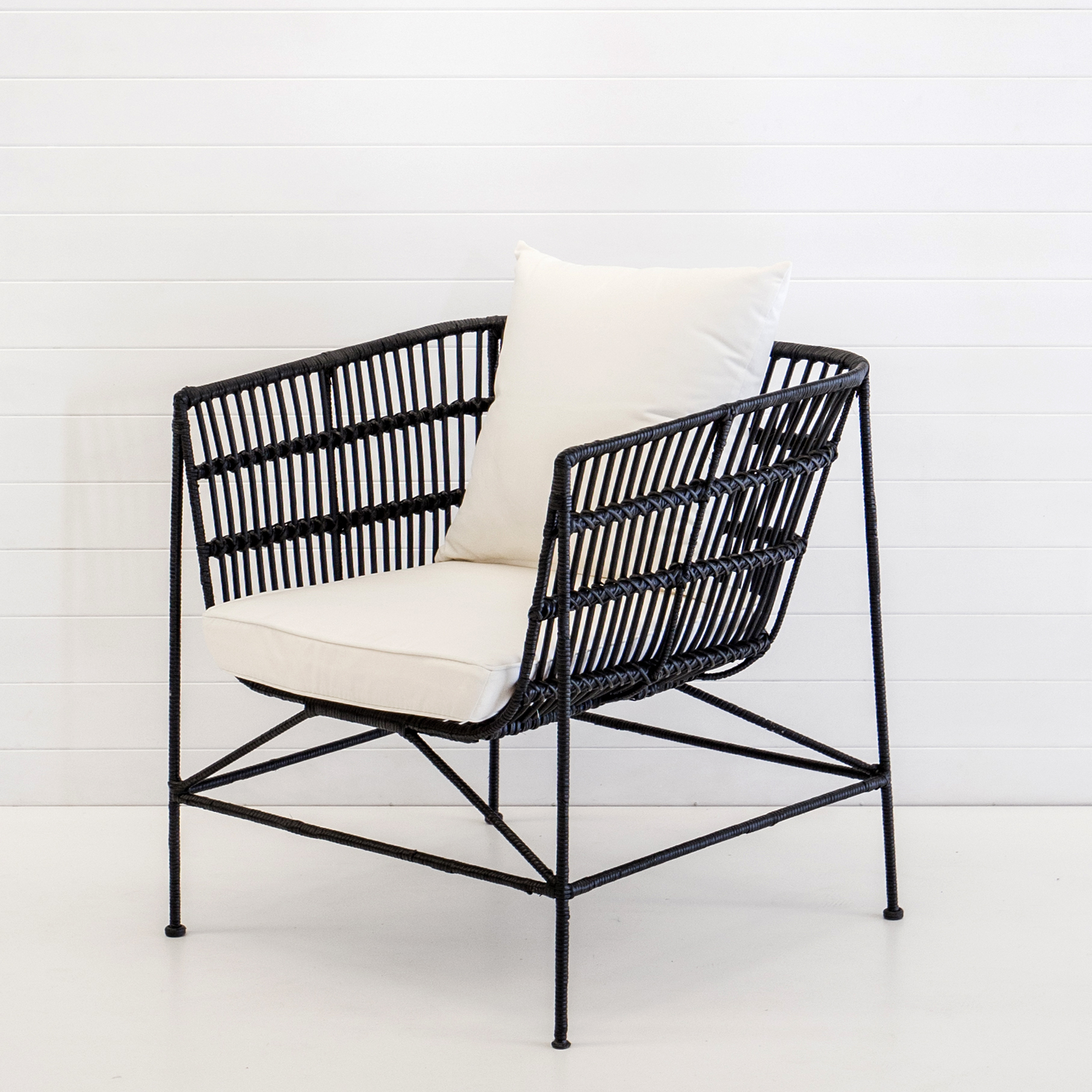 Indie black armchair with white cushions