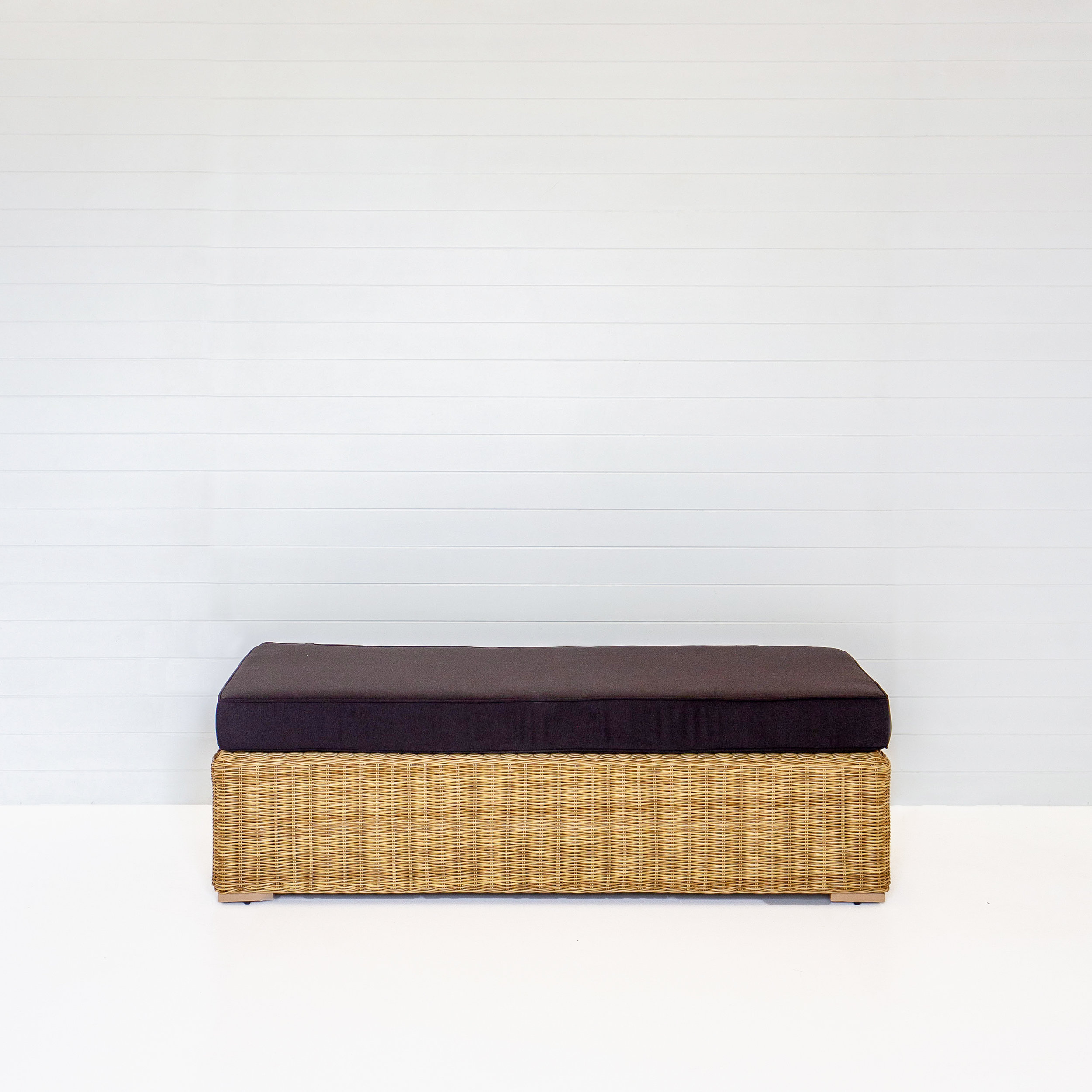 DUNE BENCH OTTOMAN WITH BLACK CUSHIONS .