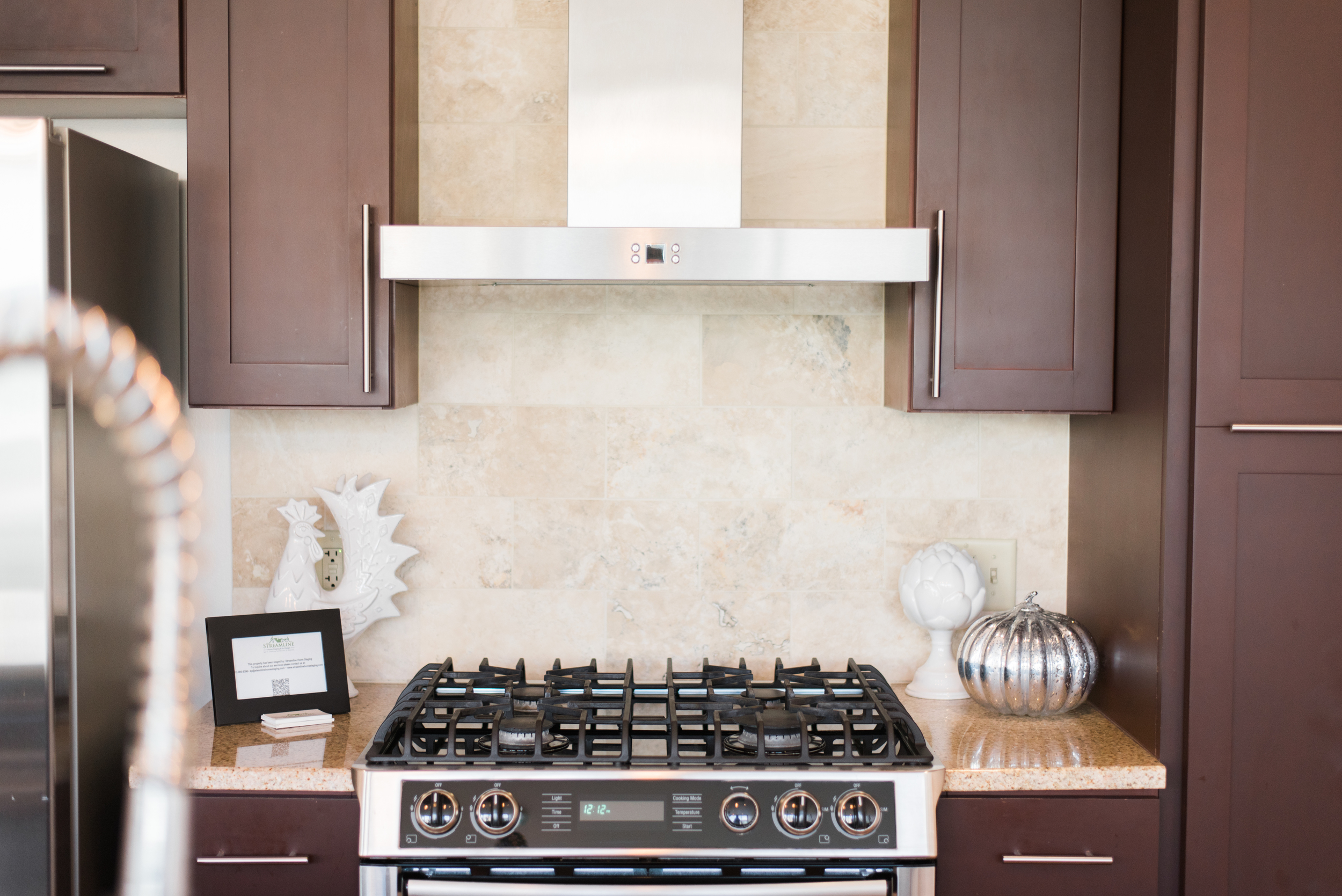 New gas stove with beautiful vent hood and cabinetry.