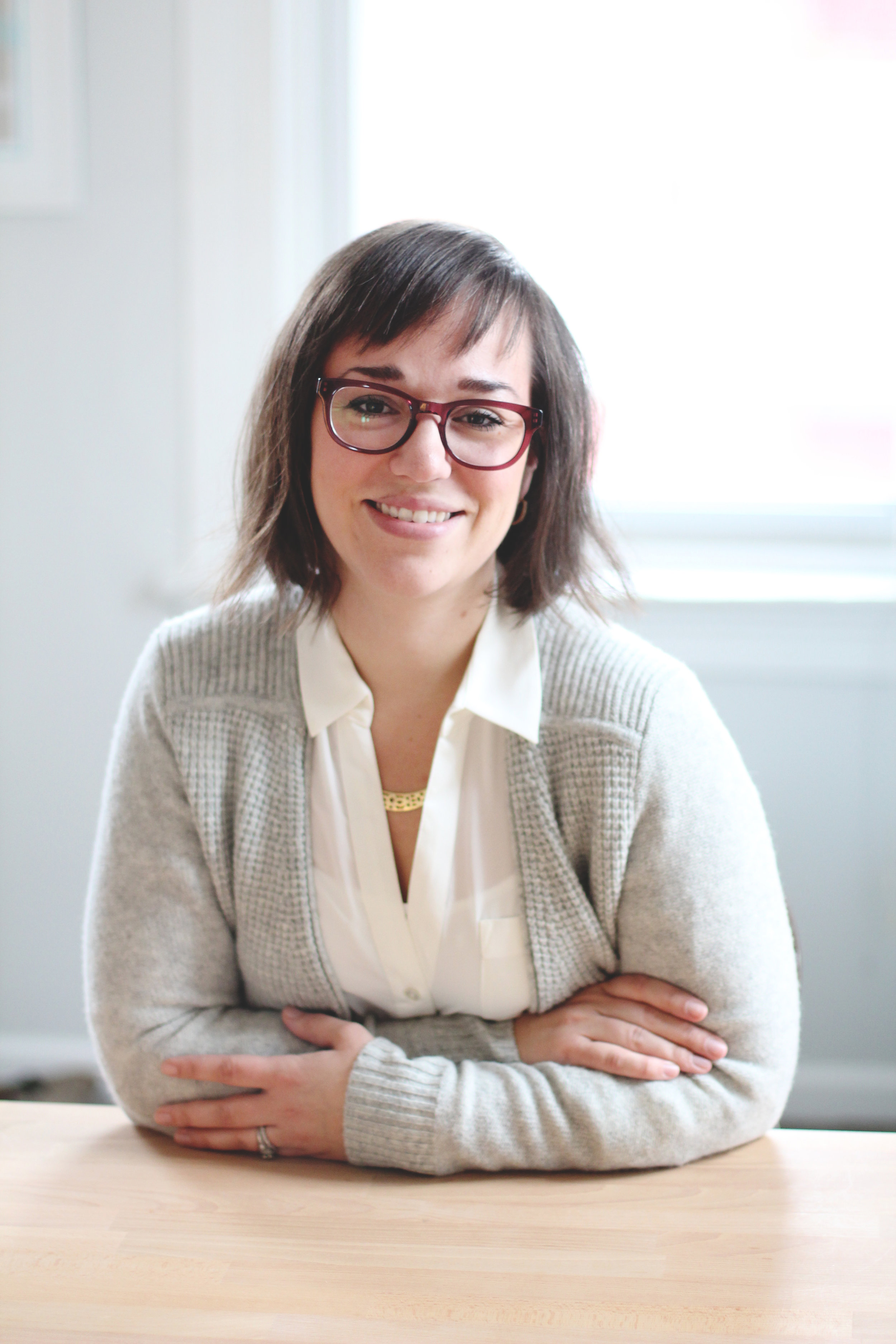 lady smiling with arms folded in front of her wearing glasses