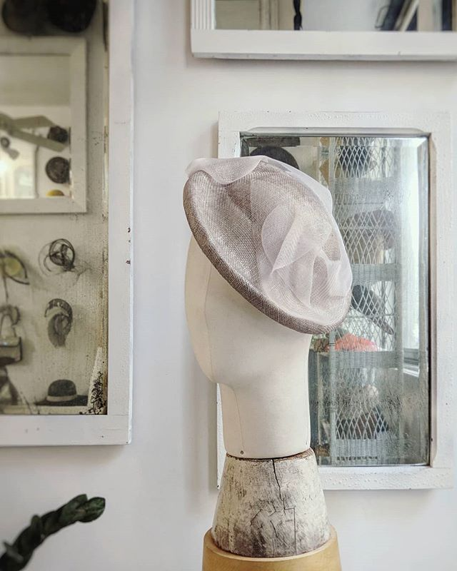 Tilt hat made from warm grey sinamay straw with the slightest tinge of pink and freeform draped crinoline trimming.