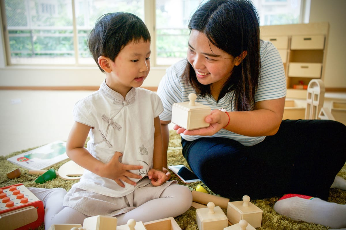 Yiuxuan He, 2 years and 10 months old, has just started at the Finnish kindergarten in Guangzhou. His teacher Lucy Lu is encouraging him to play. Picture:  Matti Hämäläinen / Yle