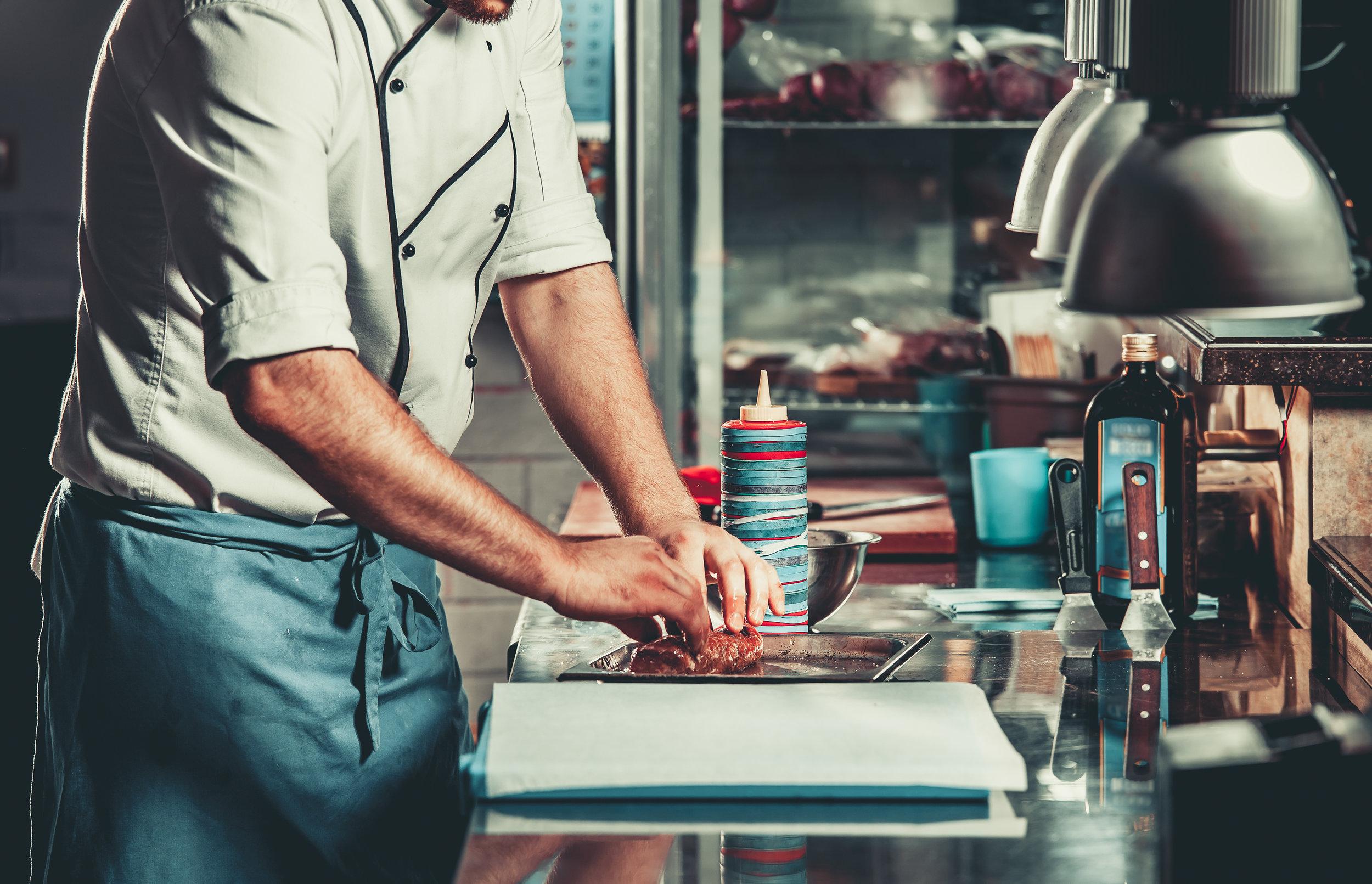 man plating food in kitchen.jpg