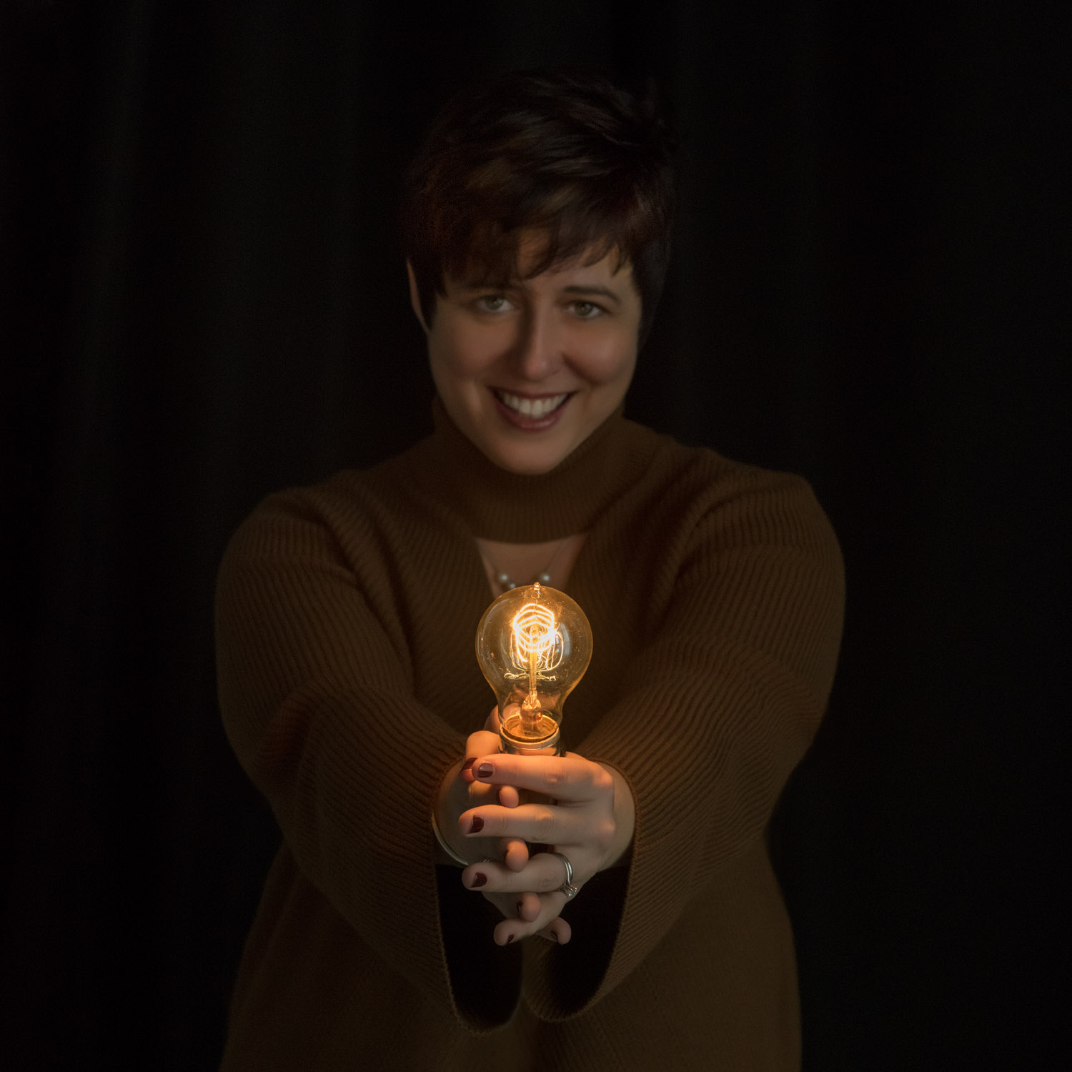 Doesn't she look a lot like Princess Di here? Jen and Princess Di share a sweet shyness and generosity of spirit.  An Edison-style light bulb is the logo for Foster Growth, and I just happen to have one in my studio. After removing it from the lamp so that she could hold it, I used Photoshop to disappear the cord.