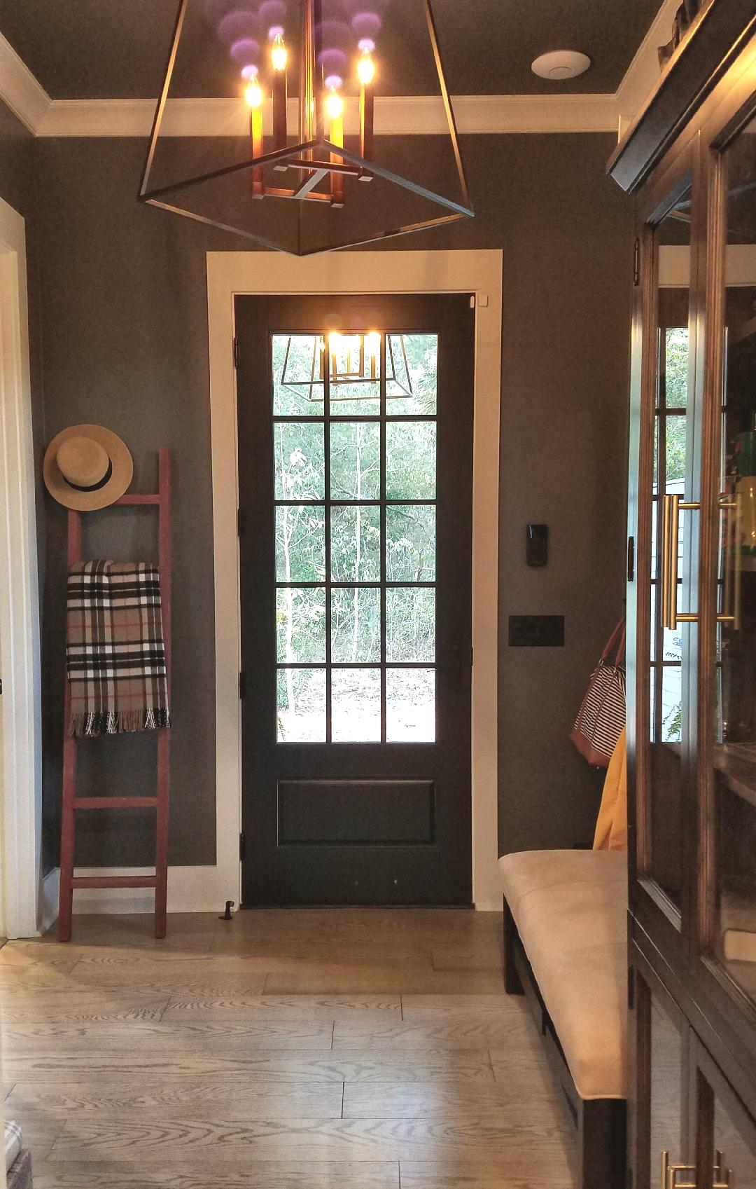 To the right of the door (above the light switch plate) in this gorgeous mudroom is the SimpliSafe keypad.