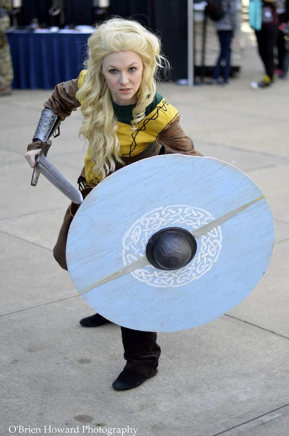 Lagertha Lothbrok- Vikings  Tunic made by me(made with faux suede with leather details sewn on. Belt, waist cincher (my first leatherwork), bracers done by me. Husband made the shield I painted it. Sword is a plastic sword leather wrapped and painted by me.    My husband looks like Ragnar! This was my first group cosplay (husband was Ragnar and our friend was Rollo) and my first group cosplay 1st place winner. We went big. We won big.    Photography by O'Brien Howard of Great Eye Photography:   www.greateyeportraits.com