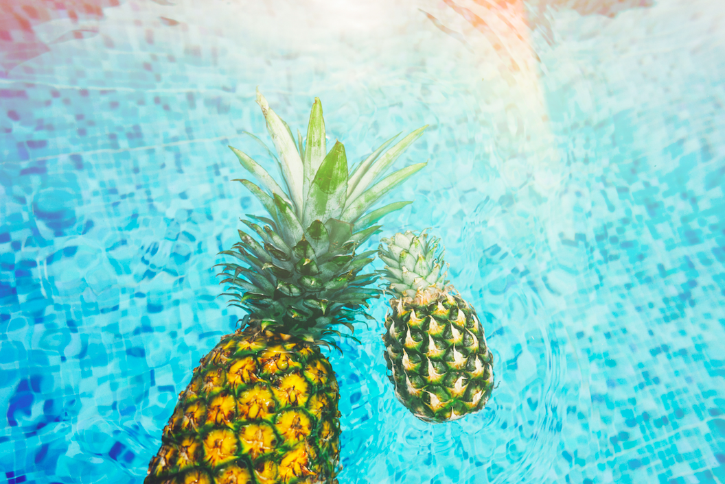 pineapples float in swimming pool