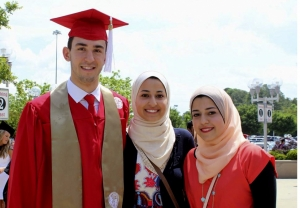 Photo Description: Two women stand center and right with a man in his red graduation cap and gown.  All three are wearing large smiles and you can see happiness in their eyes. It seems they are in a parking lot, post-graduation ceremony, with some trees, lights, signs, and cars in the background on a bright but cloudy day.