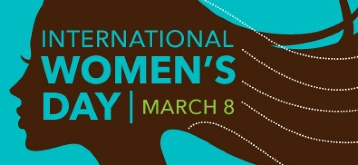 """Image Description: A wide-screen image of the dark brown silhouette of a woman laid over a mid-light grey-blue. she faces left and her hair trails over the right side of the picture. The words """"INTERNATIONAL WOMEN'S DAY, MARCH 8"""" overlay the silhouette."""