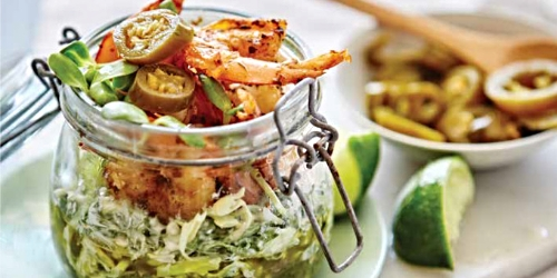 Photo Description: A glass jar is center left, with a metal lid clam, top swung open. In the jar from bottom up, salsa verde, cabbage, grilled shrimp, sunflower sprouts, and jalapeno. in a blur on a plate to the left a couple lime wedges, and behind that even more blurred, a small bowl of jalapenos with a wooden spoon.