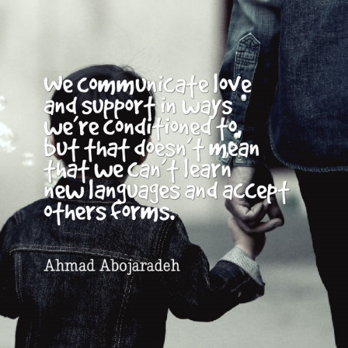 """Photo Description: A black and white photo, tinged with blue denim which a small boy and an adult wear jackets of as they appear to be walking away. The child is the focus and the adult next to them is mostly out of the picture. The child holds the adults two fore fingers. Ahmad's quote overlays photo """"We communicate love and support in ways we're conditioned to, but that doesn't mean that we can't learn new languages and accept other forms""""."""