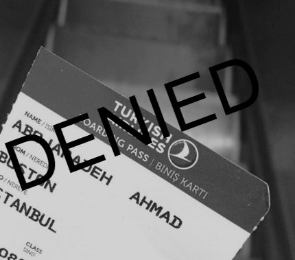 """Photo Description: A black and white image of a boarding pass of Ahmad's before a blurry staircase. The word """"DENIED"""" overlays the photo."""