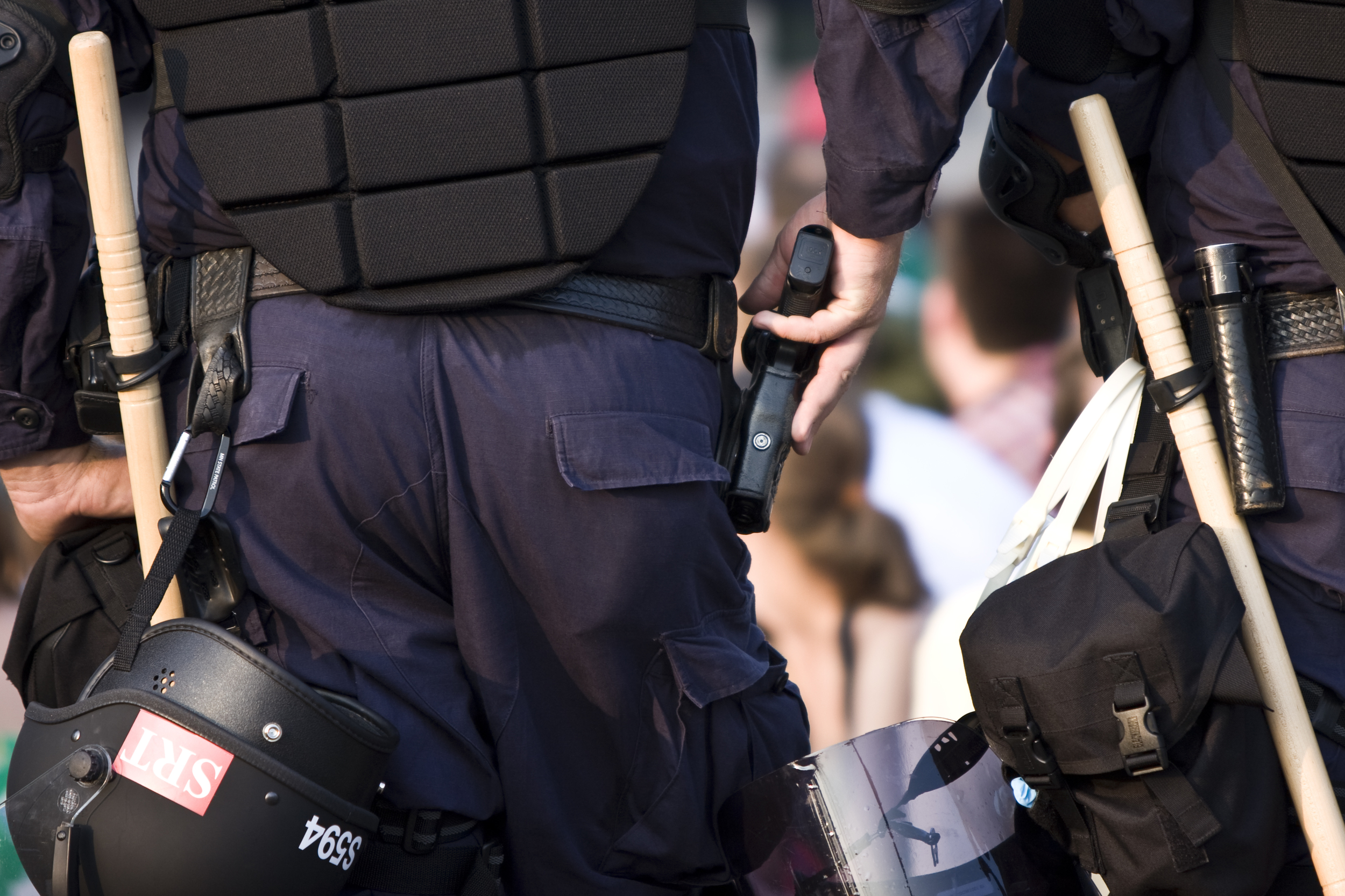 Photo Description: A rear-view of two police officers standing before a blurry crowd. The officer to the left has his hand on his gun. They are both equiped with weapons, armor, and helmets.