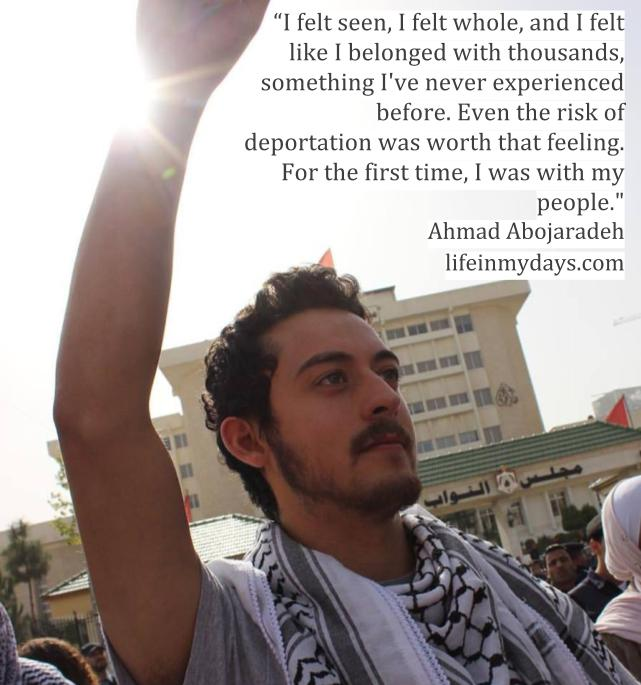 I stand in the sunlight, hands held high, with a Palestinian Keffiyeh around my neck.