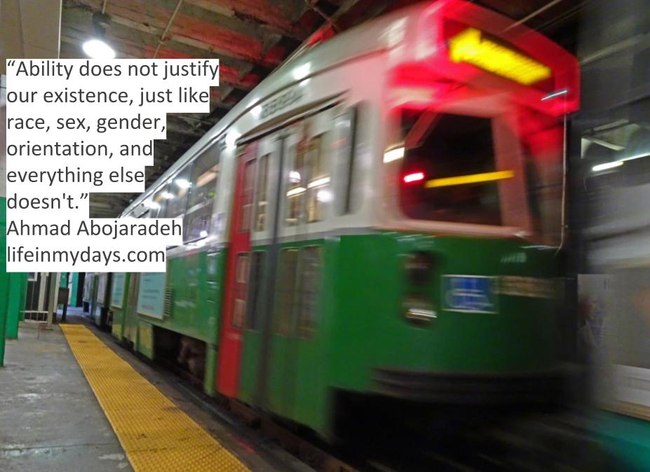 Photo Description: A green subway train in boston blazes past with a disabilities sticker blurred out in the front.