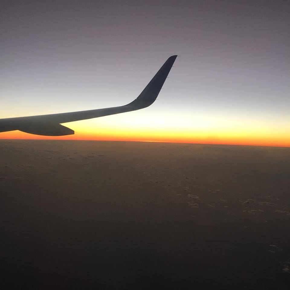Photo Description: The sun sets below the right wing of a plane over Puerto Rico.