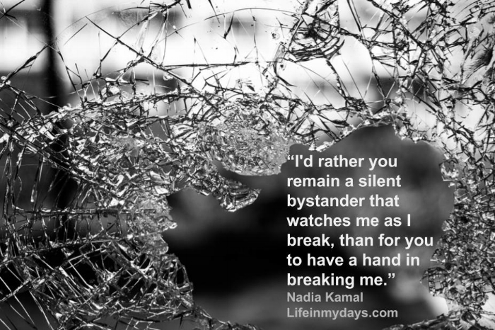 """Shattered glass from a window with the following quote from Nadia Kamal """" I'd rather you remain a silent bystander that watches me as I break, than for you to have a hand in breaking me."""""""