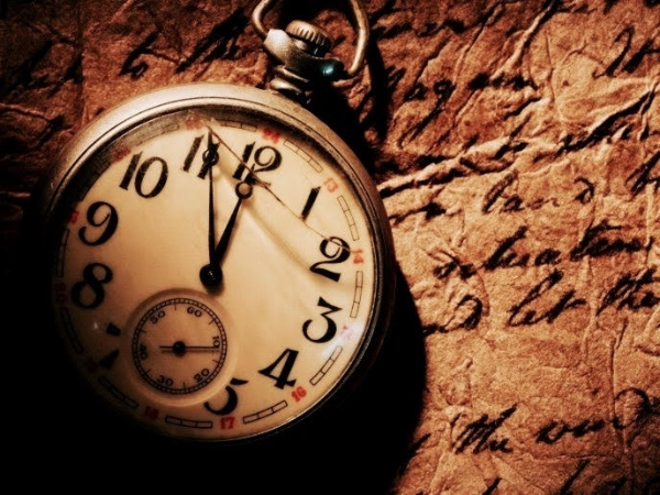 A cracked pocket watch set at 11:55 sits a top wrinkled brown paper with cursive writing.
