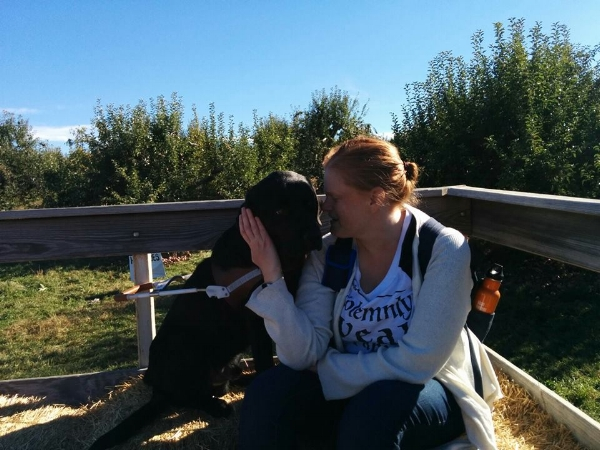 Photo Description: Sarah stares into Ferdie's eyes as they enjoy a hayride in an apple form, with beautiful blue sky in the background.