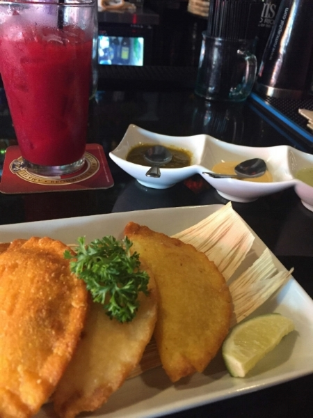 Photo Description: Three crisp fried samosas topped with a large piece of parsley, atop a dried corn husk, with a lime garnish in the forefront. Behind, to the right three dishes containing little spoons and various sauces. To the left behind, a dark red beverage with ice and a straw in a pint glass.