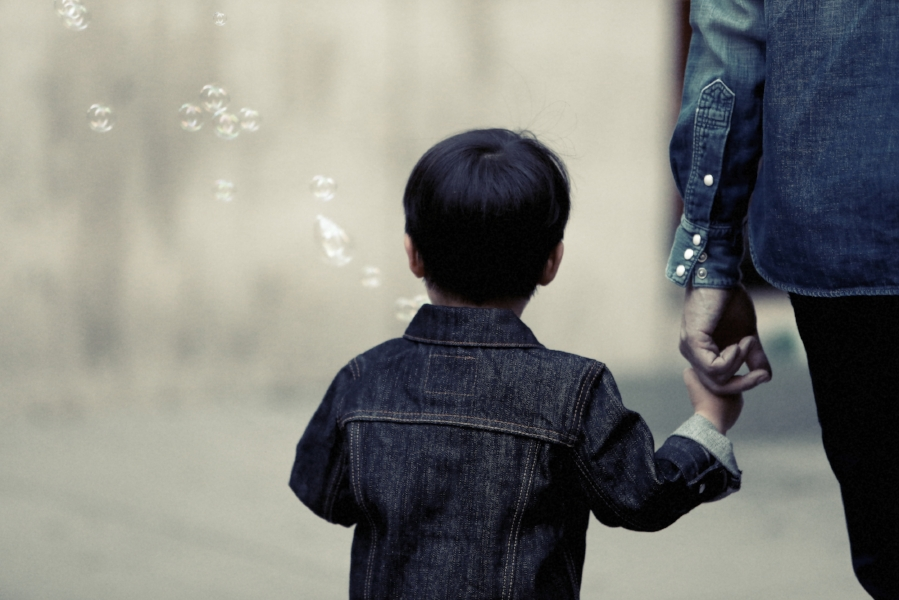 Photo Description. I near black and blue photo with blue tint. A small child is center focus, visible from waist up. The child holds the pointer and middle finger of an adult, to their right. Both hear denim shirts. The child appears to be blowing bubbles, as there is a stream of blurred bubbles blowing up and to the left.