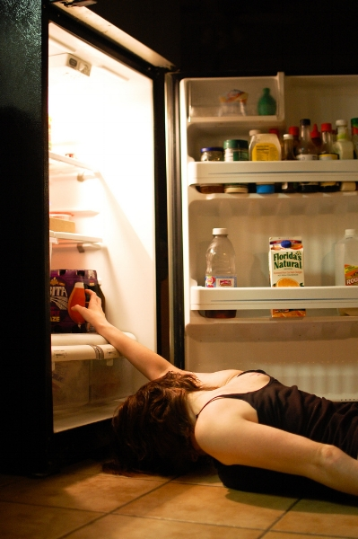 Photo Description: A woman lies before an open fridge with her face face-down on the tile and one arm reaching in to grab a beer.  She appears to be sleeping.