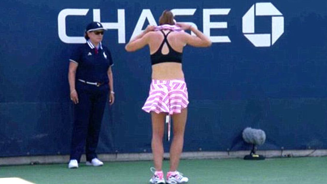 This is the moment Alize Cornet inspired the tennis court umpire to penalize her for removing her top to switch it around.