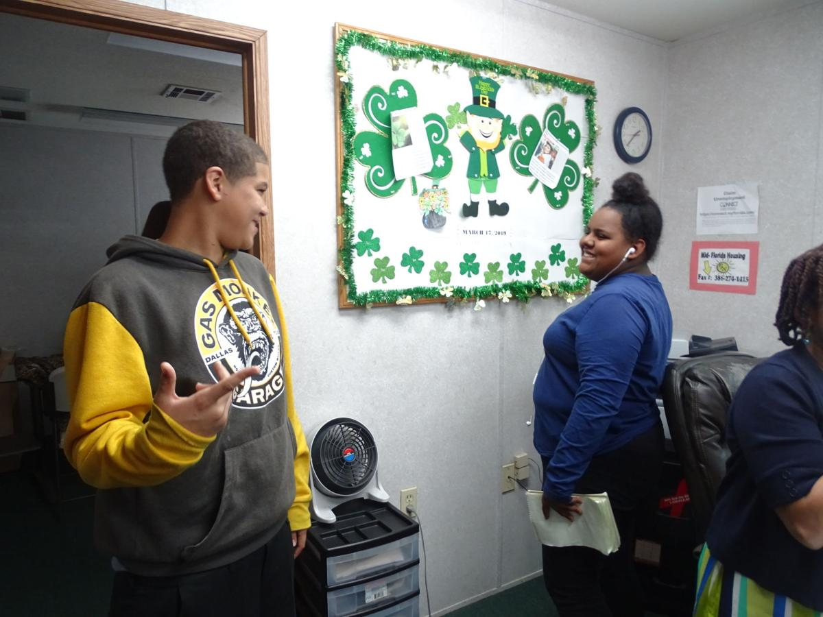 """Students— Students from nearby grade schools also use the Resource Center. Some, like middle-school students Cameron Doby, left, come by every day after school. """"We're like mentors,"""" Administrator Shilretha Dixon said. At right is DeLand High School sophomore Soraya Gonzalez.  BEACON PHOTO/ELI WITEK"""