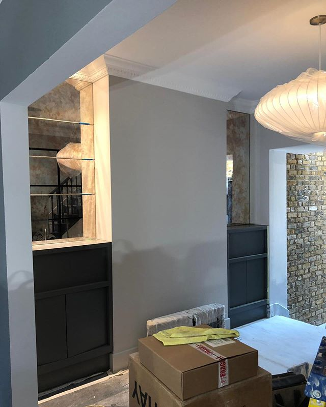 Pre moving in shot of a clients amazing home. These are the existing units, painted in a new colour, with antique mirror added above and 2 @hermanmiller bubble saucer lights. You can see the reflection of the crittall wall in the dining room. This one is going to be a beauty #interiordesign #design #crittallwall #joinery #brickwall #hermanmiller