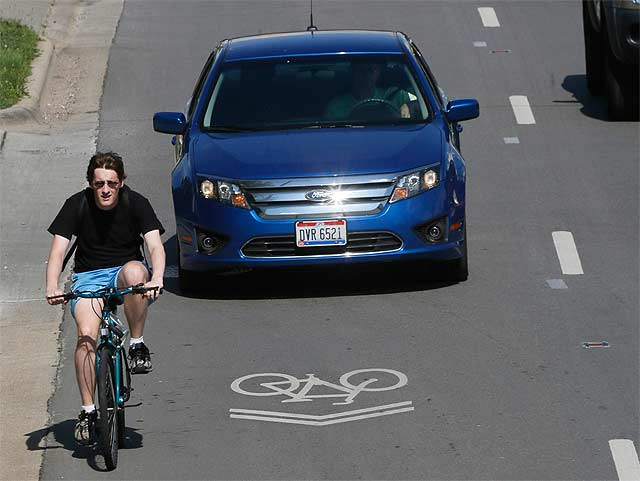 Point taken: a cyclist who clearly does not understand what that sharrow is for (i.e., to help him position himself correctly in the lane). Source:  dispatch.com .