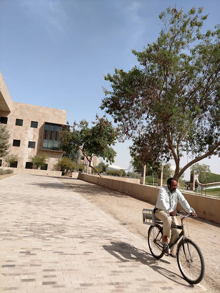 A person navigating Education City by bike.