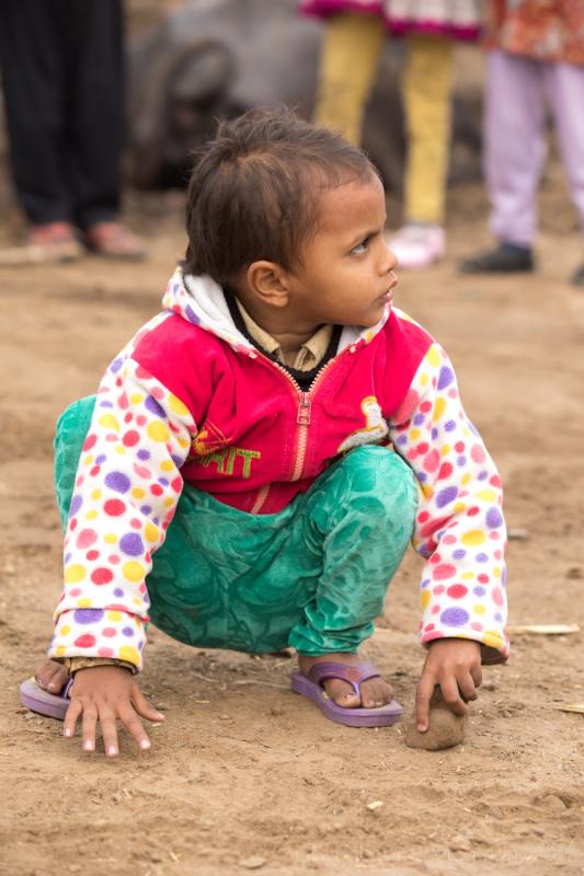 Girl crouching down,Boy in green top, Mathura, Uttar Pradesh, India