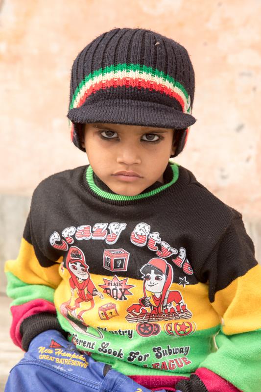 Serious boy in peaked hat,Smiling boy in leather jacket, Mathura, Uttar Pradesh, India