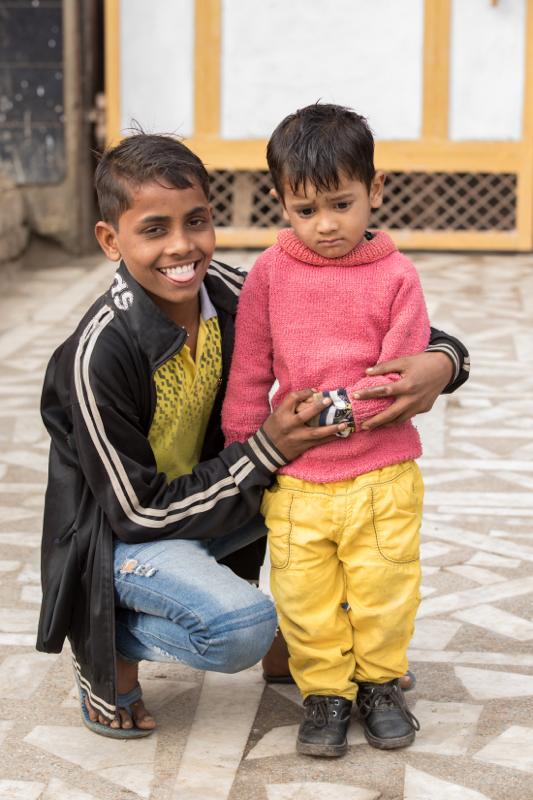 Boy cuddling child in pink jumper, Mathura, Uttar Pradesh, India