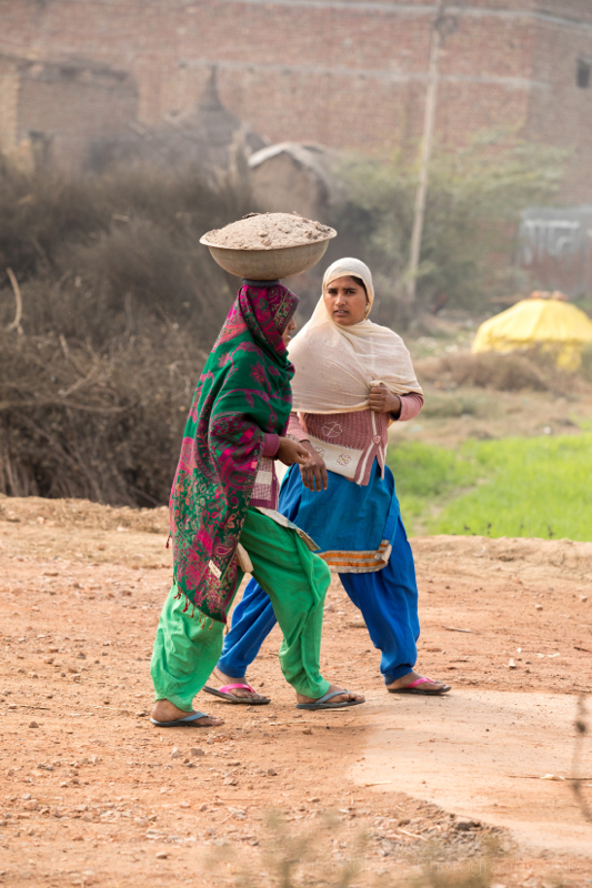 Woman chatting & carrying bowl of cement on her head, Palwal, India