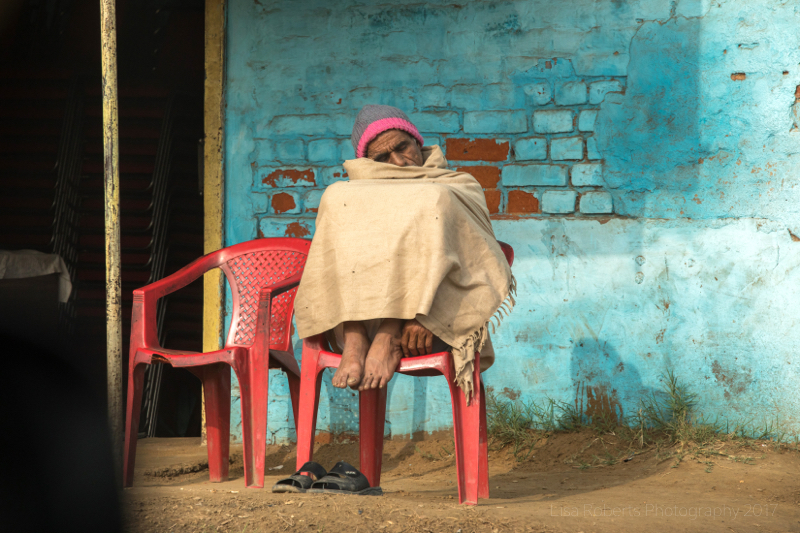 Man snoozing on red chair, Palwal, India