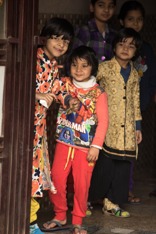 Children peeping around the doorway, Palwal, India