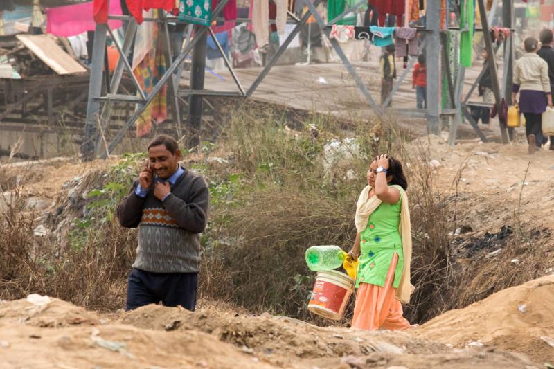 Man on mobile & woman in green in New Delhi Slum, India