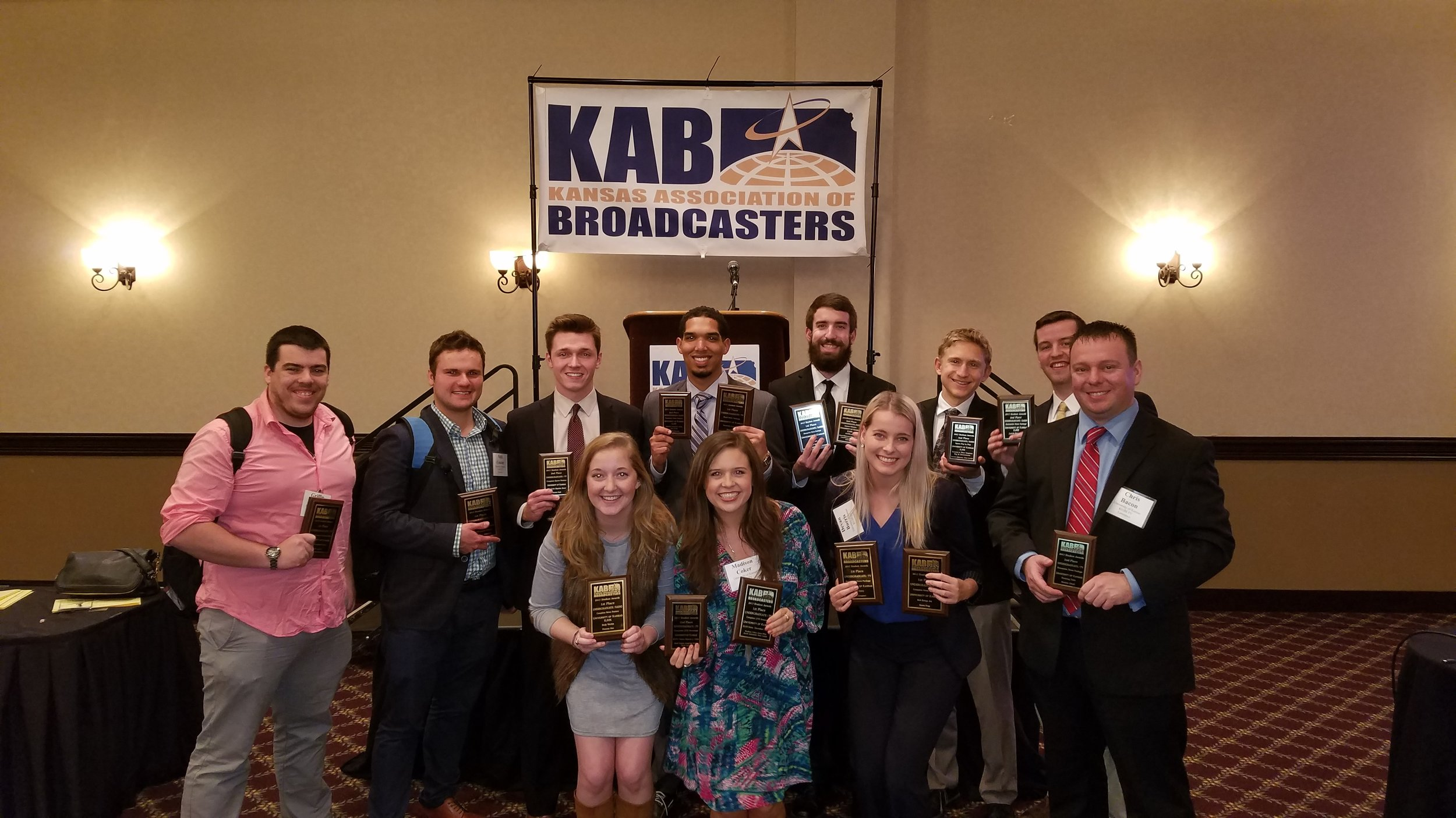 Fourteen J-School students attended the Kansas Association of Broadcasters Student Seminar on April 4 and picked up their broadcast awards. Pictured are: (Back row)  Griffin Hughes, Nick Couzin, Alex McLoon, Alden German, Shane Martin, Carson Vickroy  and  Jacob Asherman . (Front row)  Alana Flinn, Madison Coker, Devan Burris  and  Chris Bacon . Not pictured:  Associate Professor Max Utsler, Marissa Khalil  and  Libby McEnulty .