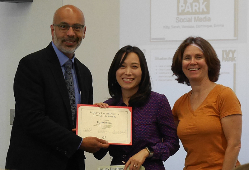 Associate Professor Hyunjin Seo received the 2017 Faculty Excellence in Service Learning Award from the KU Center for Civic and Social Responsibility (CCSR). CCSR Director John Augusto and Assistant Director Linda Dixon made a surprise visit to her J615 Social Media class May 2 to present the award.
