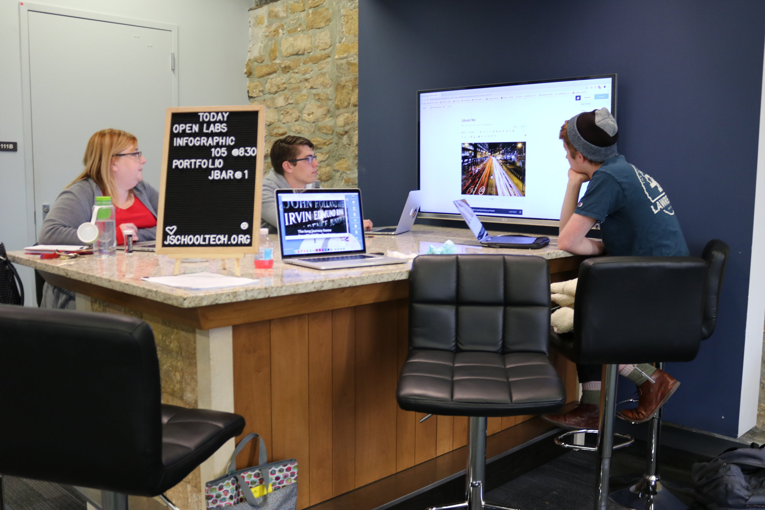 Heather Lawrenz (j'96), J-School digital media specialist, assists students with questions about infographics.