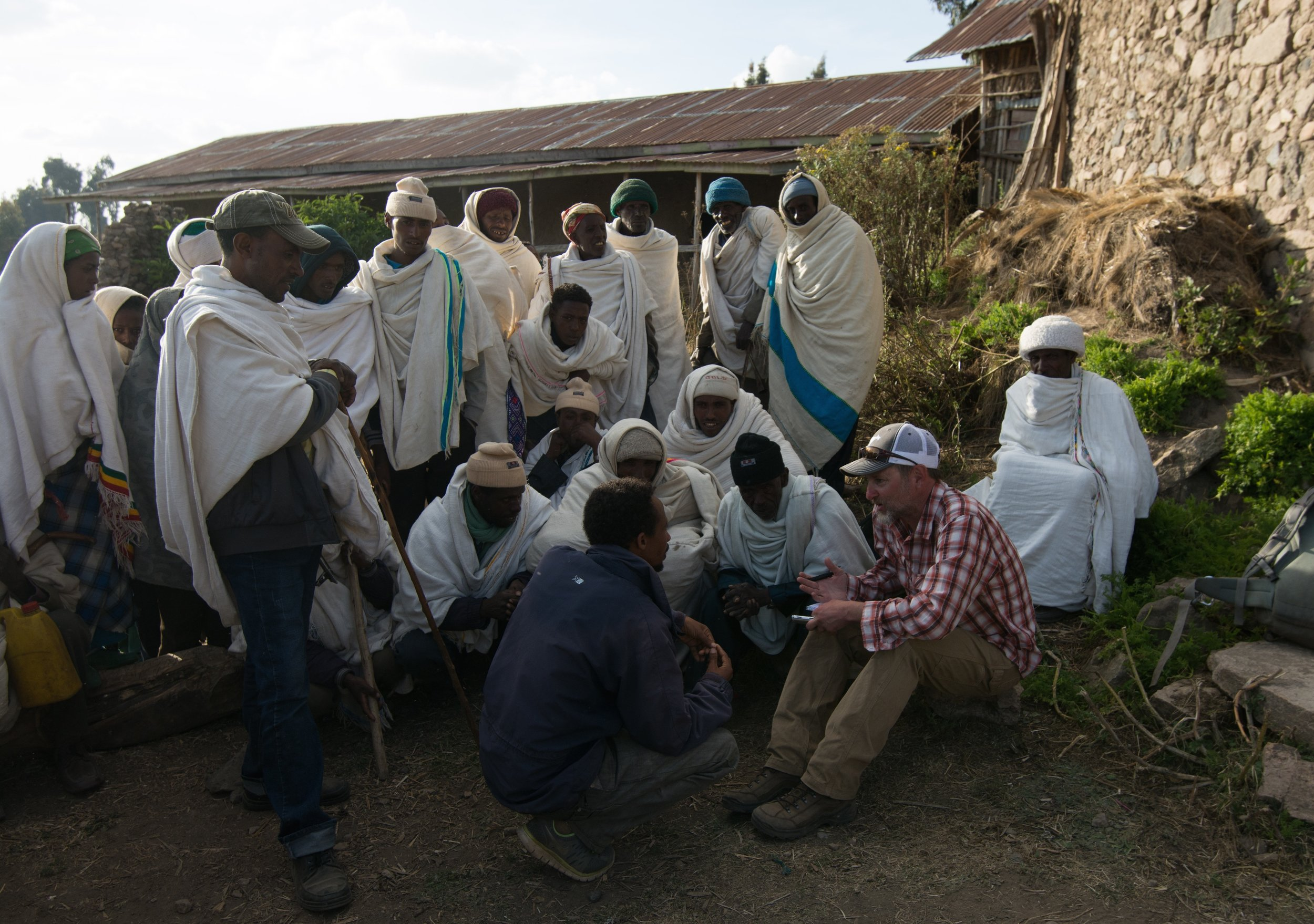 Christian villagers outside a church explain to Welch how they've managed to so thoroughly protect the rich grasslands in their community of 45,000 in the highlands of Ethiopia—a place where most meadows, thickets, moors and swamps are in steep decay. PHOTO CREDIT: Jeff Kerby