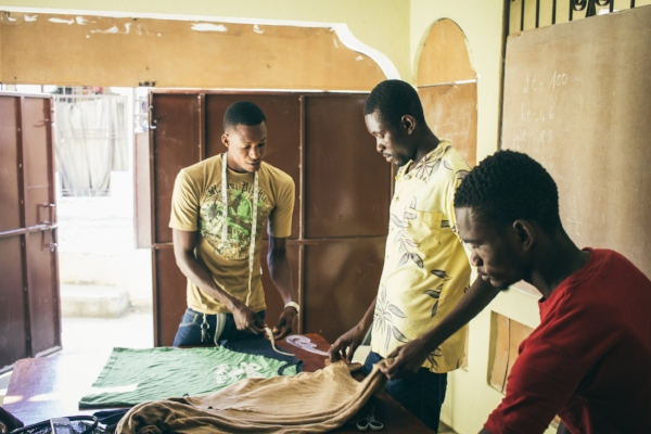 Students in the Port-de-Paix sewing class measure fabric for a new project.  Photo by    Taylor Davis.