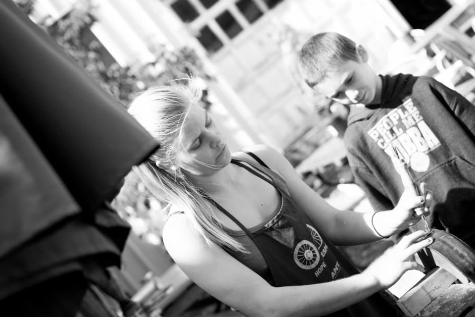 Emily Jensen teaching a local kid how to patch a tube. Photo Credit to Brenna Ellis Photography