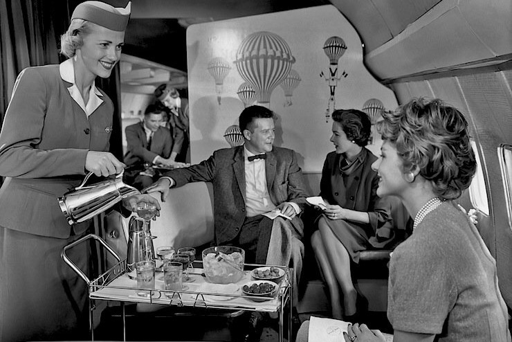1950s PanAm stewardess using a bar cart to serve passengers.